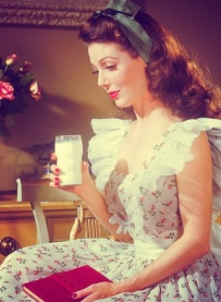 Portrait of American film and television actress Loretta Young (1913 - 2000), as she sits on a chair, a glass of milk in one hand and a red book in her lap, dressed in a flower print dress with lace accents and a large bow at the back, late 1940s. (Photo by Bob Landry/Time & Life Pictures/Getty Images)