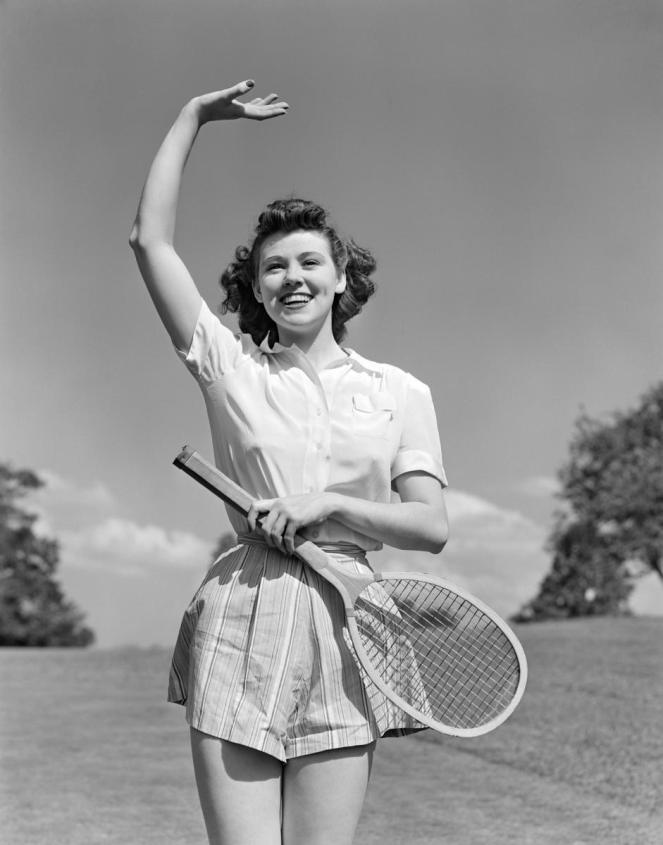 1930s 1940s woman tennis player waving smiling holding racket