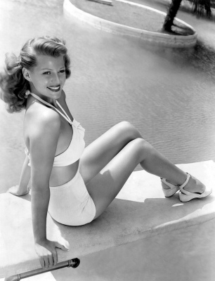 1945: Actress Rita Hayworth posing in white two-piece bathing suit as she sits on deck at the edge of her enormous swimming pool at home. (Photo by Peter Stackpole)