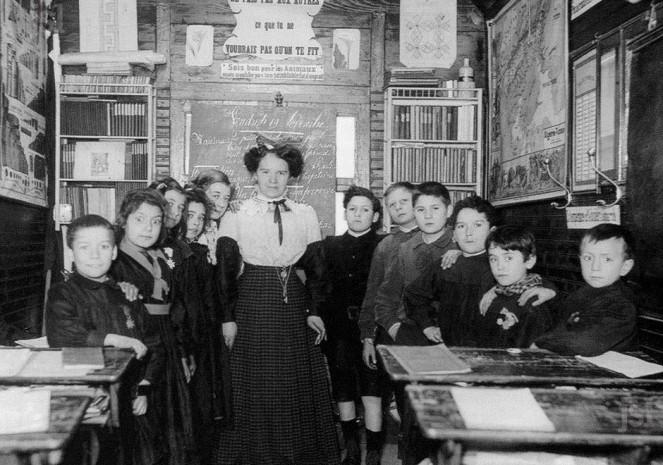 l-interieur-d-une-classe-vers-1900-a-noter-la-croix-d-honneur-sur-la-blouse-de-l-ecolier-a-gauche-au-1-er-plan-et-sur-celle-de-la-2-e-fillette-a-sa-droite-illustration-dr-1462194157